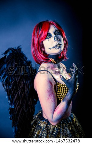 Beautiful sensual girl wearing Halloween costume with black wings and skull makeup on a dark background