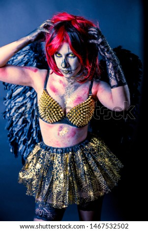 Beautiful sensual girl wearing Halloween costume with black wings and sugar skull makeup on a dark background