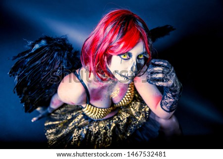 Beautiful sensual girl wearing Halloween costume with black wings and sugar skull makeup sitting on a dark background. Shallow depth of field.