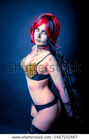 Beautiful sensual girl wearing spikes bra with black wings and sugar skull makeup on a dark background