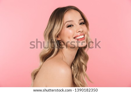 Beautiful sensual topless woman with long blonde hair standing isolated over pink background, posing
