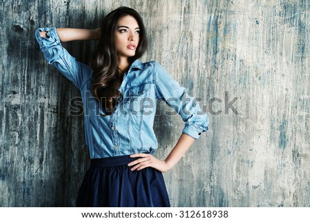 Beautiful sensual woman in jeans clothes stands by the grunge wall. Fashion.