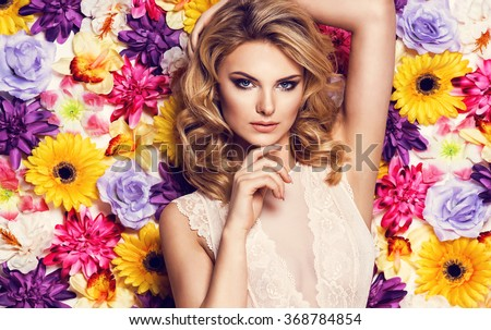 Beautiful sensual woman in laced lingerie on colorful wall of flowers. Beauty photo, nice hair