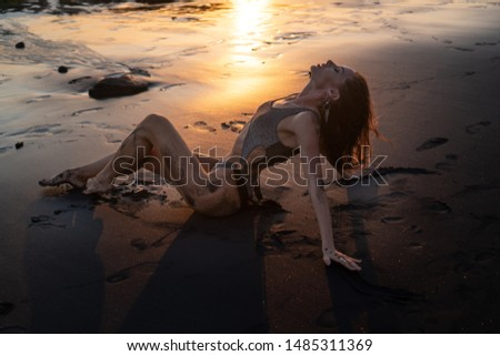 Beautiful sensual woman in sparkling swimsuit posing at the black sand beach during amazing golden sunset