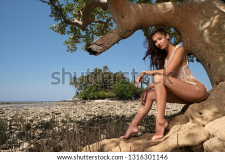 Beautiful  sensual woman sitting on the tree branch over tropical island and summer sky background