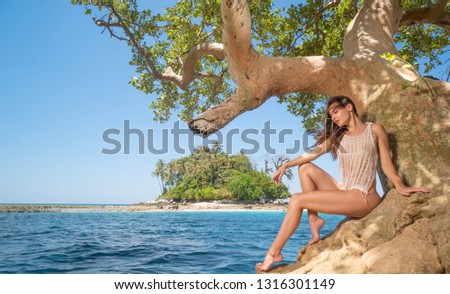 Beautiful  sensual woman sitting on the tree branch over tropical island, blue sea water and summer sky background