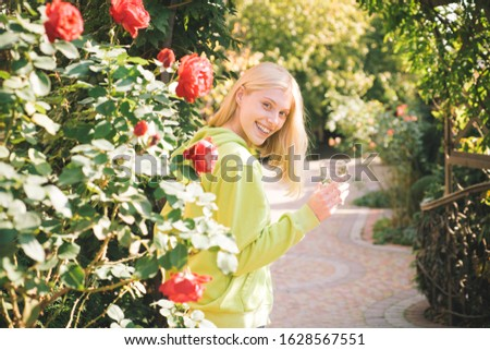 Beautiful sensual woman standing behind hot red roses and holding glass of fresh water. Active lifestyle at autumnal park. Fall leafs background. Sunny warm autumn day. Autumn concept
