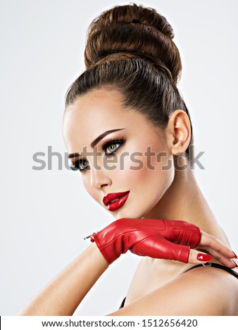 Beautiful sensual woman with glamour makeup. Pretty sensual young adult girl in red leather gloves