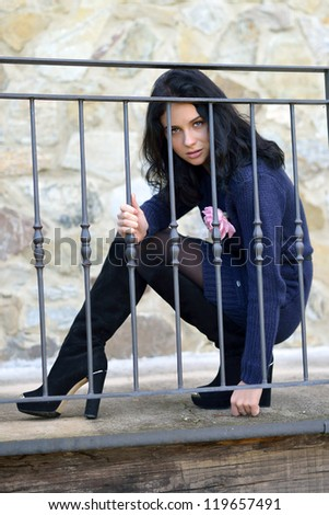Beautiful sensual young woman with aggressive  glance behind the iron fence of the old house, Tuscan, Italy