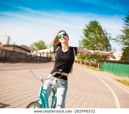 beautiful sensuality elegance haired hair woman happy fun cheerful smiling blue sunglasses black t-shirt jeans bicycle urban city portrait nature slim sport body hobby equipment riding bike cyclist  #282998552
