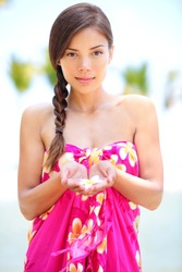 Beautiful serene woman on beach in sarong holding flower in palm of hands. Portrait of pretty graceful mixed race asian young woman on travel vacation on Hawaiian beach, Hawaii, Big Island, USA.