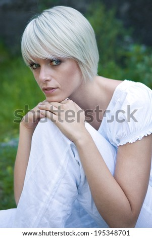 Beautiful serene young blond woman sitting enjoying the freedom of nature resting her chin on her knee looking sideways at the camera with a calm expression