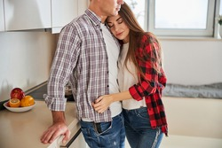 Beautiful serene young Caucasian female with closed eyes leaning her head against her husband chest