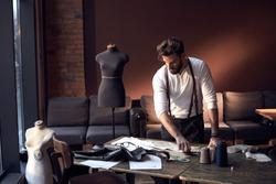 Beautiful serious tailor with glasses in white shirt with brown leather suspenders working near wooden table with threads, apron and scissors in amazing atelier with antique furniture and mannequin
