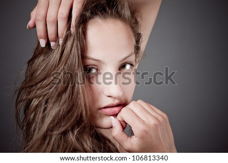 beautiful serious young girl with brown hair on gray background