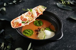 Beautiful Serving Lobster Bisque with Crab Meat in it Leg. Exquisite Dish of Seafood Chowder or Gourmet Shellfish Soup on Natural Black Stone, Leaves, Flowers and Fruits Background
