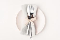 Beautiful set of cutlery knife and fork on a plate on a white wooden table. Concept of Thanksgiving, Christmas, or other holiday.