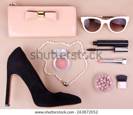 beautiful set of women\'s fashion accessories and cosmetics on a beige background
