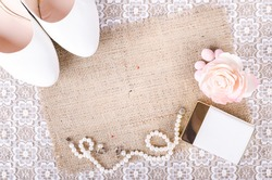 Beautiful set of women's wedding accessories. Bride's morning. White shoes, perfume, pearl necklace and earrings on white lace cloth and sackcloth, canvas.