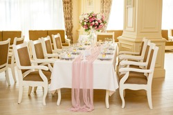 Beautiful setting of wedding or birthday party in restaurant. Table decorated with flowers. Elegant cafe decoration. Wedding party banquet