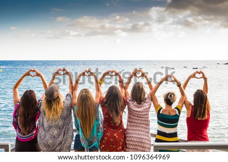 beautiful seven girls from the backside doing a heart with the hands looking at the ocean waiting the sunset in vacation leisure activity. friendshipt all together forever concept, travel to sea party