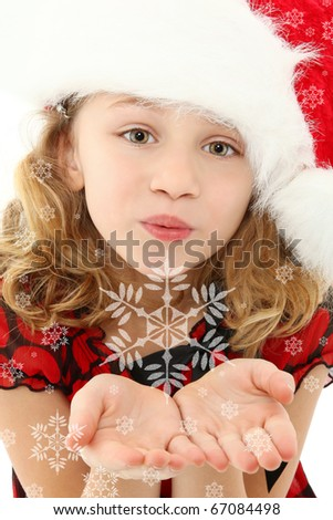 Beautiful seven year old girl in santa hat blowing snowflakes to camera.