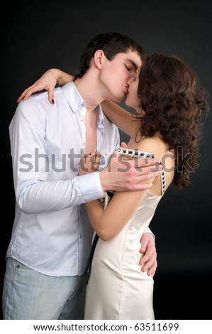 Beautiful sexual couple kissing over black background