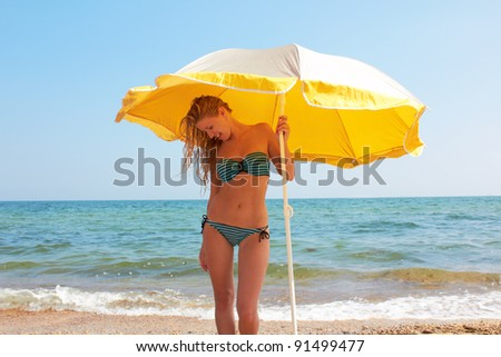 Beautiful sexual girl blonde pose on beach in swimsuit