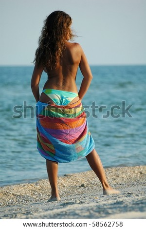 Beautiful sexual girl brunette topless with towel on beach