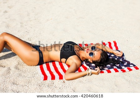 Beautiful sexy amazing woman in black bikini, lay on sand, fashionable outfit, trendy apparel, golden fashion dress, accessories, close up toned body, details. American summer style, LA, Fancy
