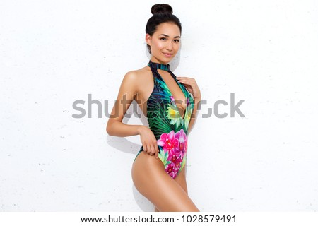 Beautiful,Sexy asian girl  standing on isolated on white background in a colors bathing suit bikini and smiling.perfect for photo advertisements, style vogue