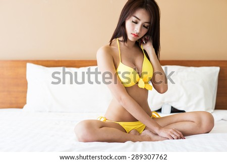 Beautiful sexy asian woman in bright yellow bikini posing in her bedroom