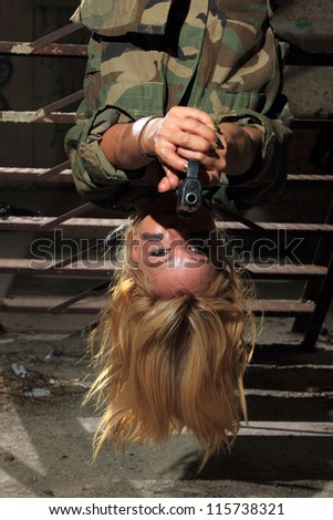Beautiful sexy blond woman with gun hanging upside down