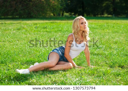 Beautiful sexy blonde woman dressed in a denim blue shorts. Fashion model in jeans clothing. Summer park outdoor
