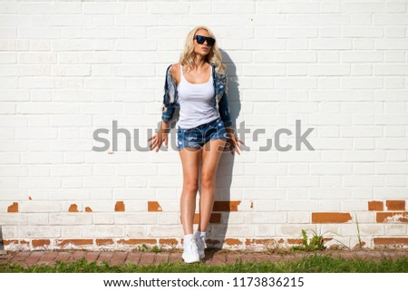 Beautiful sexy blonde woman dressed in a denim jacket and shorts. Fashion model in jeans clothing. White brick wall outdoor