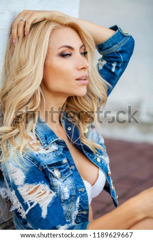Beautiful sexy blonde woman dressed in a denim jacket. Fashion model in jeans clothing. White brick wall outdoor
