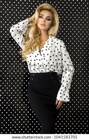 Beautiful, sexy blonde woman in elegant clothes in polka dots