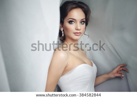 Beautiful sexy bride in white dress posing under curtain