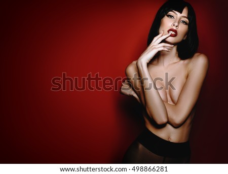 Beautiful sexy brunette girl posing nude in black stockings and shoes in the studio on a red background. Advertising Space #498866281