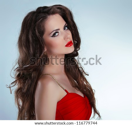 Beautiful sexy brunette girl with red lips and curly hairs in dress