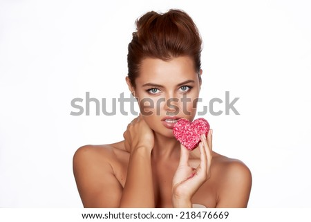 Beautiful sexy brunette woman eating cake shape of heart on a white background, healthy food, tasty, organic, romantic valentine day