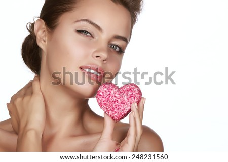 Beautiful sexy brunette woman eating cake shape of heart on a white background, healthy food, tasty, organic, romantic valentines day