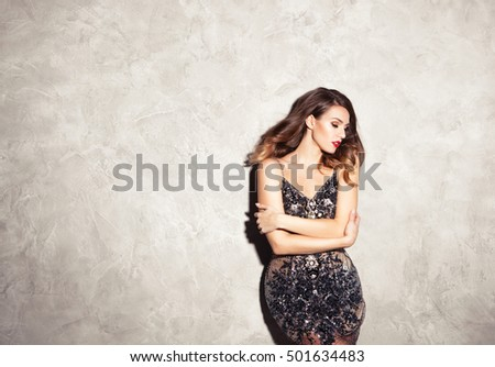 Shutterstock Beautiful sexy brunette woman on grey  background, in sparkly dress  party.