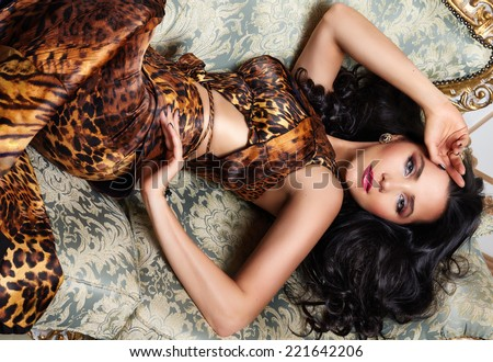 Beautiful sexy brunette woman with wavy hair in a bright multi-colored suit wild animal dress with rings bracelets accessories, or evening hairstyle and makeup lying on the bed with cushions