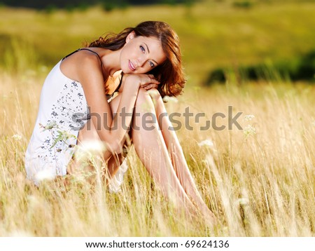 Beautiful  sexy caucasian woman sitting on the grass on summer meadow
