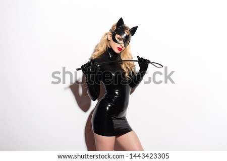 Beautiful sexy dominant vamp mistress dominatrix bdsm doll face blonde woman model in glamour black latex dress, sex shop style, and fetish leather cat mask posing on white background