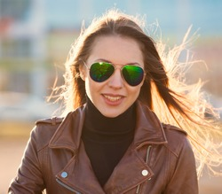 Beautiful sexy elegance haired hair woman, has happy face, brown leather jacket, sunglasses. Has slim sport body. Portrait in the street urban city. Aviator sunglasses