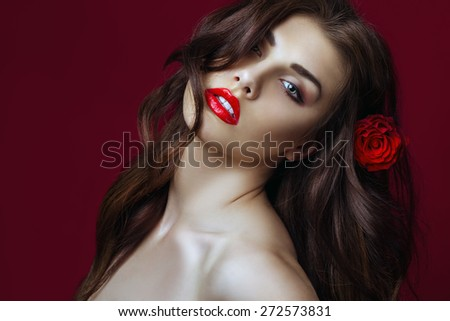 Beautiful Sexy fashion Woman with rose in her hair.  Makeup with Red Lips, long perfect hair and Red rose. Beauty italian Girl. Passion. Close up. Copy space
