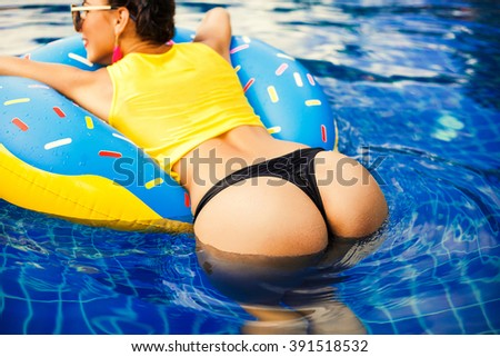 Beautiful sexy girl in a bathing suit swims in the pool on an inflatable circle in the form of a donut. Back view