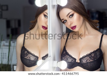 beautiful sexy girl in lacy lingerie with bright makeup smokey eyes with big puffy lips with big breasts standing near mirror #411466795